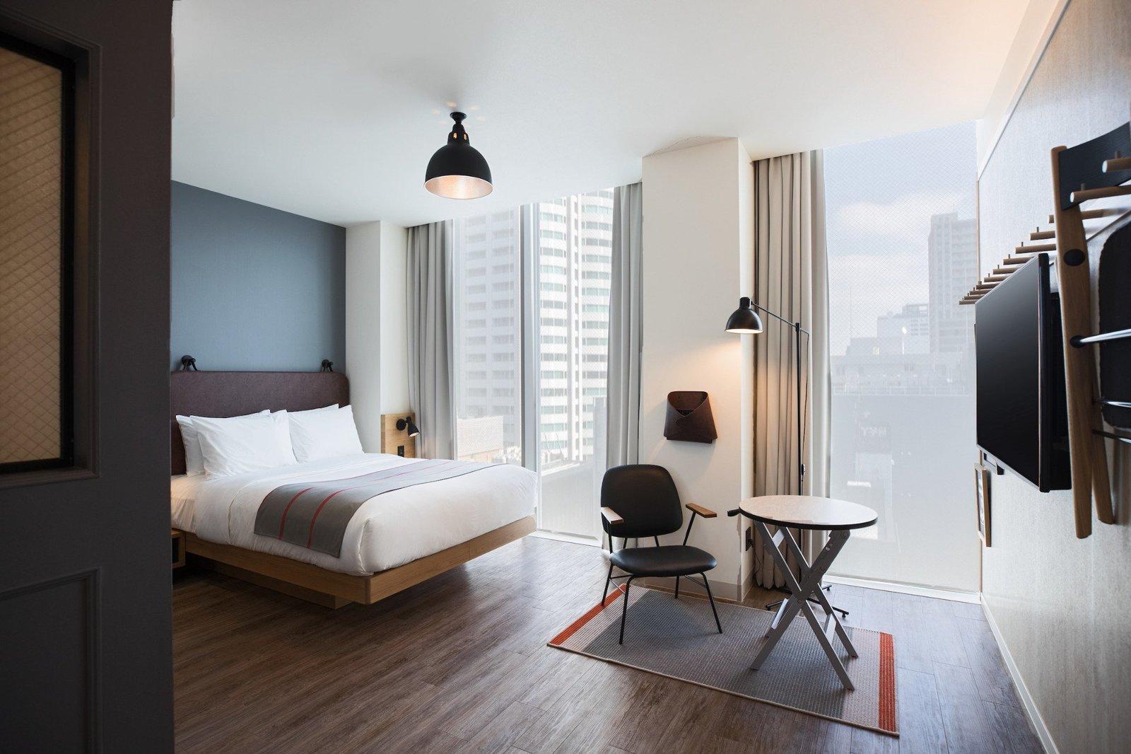 Bedroom, Chair, Rug Floor, Wall Lighting, Bed, Dark Hardwood Floor, Ceiling Lighting, and Floor Lighting  Moxy Osaka Honmachi