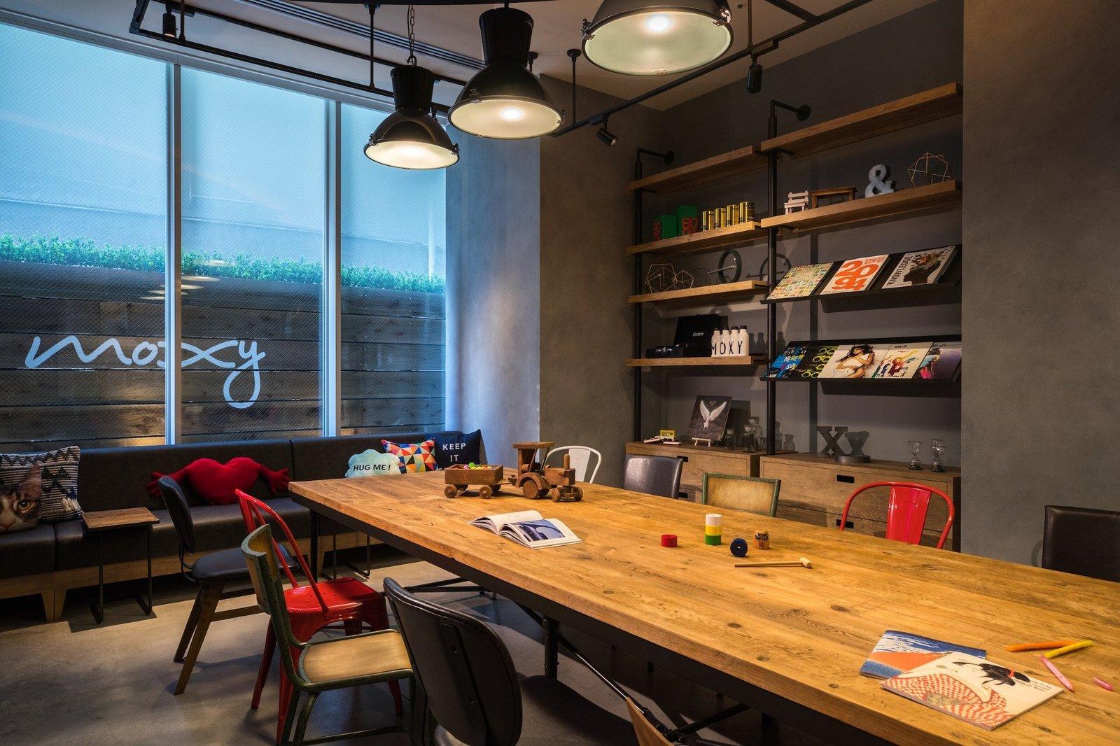 Living Room, Table, Pendant Lighting, Shelves, Concrete Floor, Chair, and Sofa  Moxy Osaka Honmachi