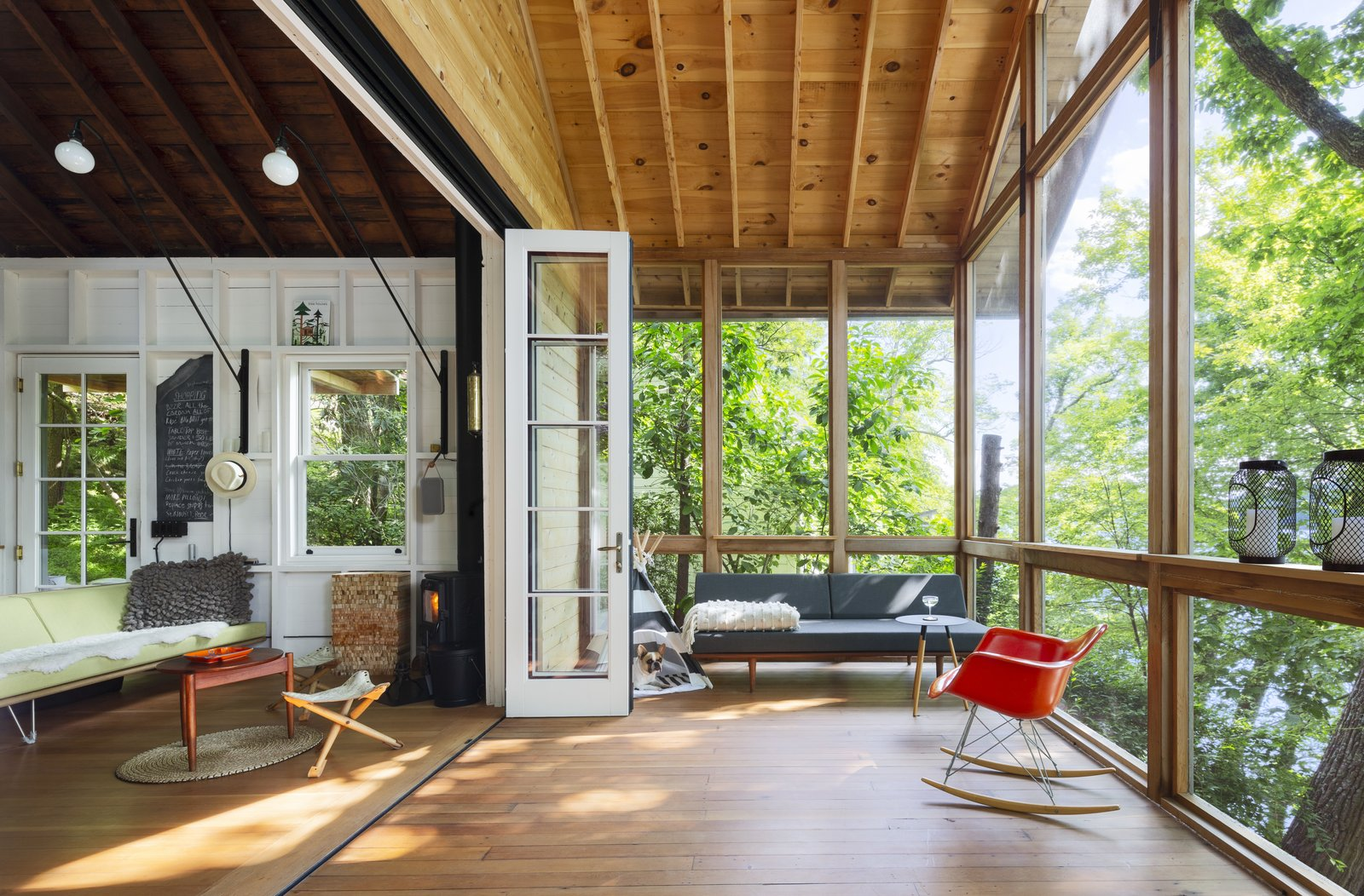 Living Room, Wood Burning Fireplace, Rug Floor, Coffee Tables, Chair, Sofa, Medium Hardwood Floor, and Wall Lighting  Photos from This Lakeside Cabin in New York Is Offbeat in the Best Way