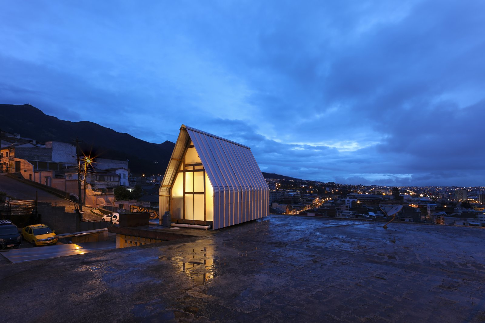 Exterior, House Building Type, A-Frame RoofLine, Metal Roof Material, Glass Siding Material, Wood Siding Material, Gable RoofLine, Metal Siding Material, and Tiny Home Building Type  Best Photos from This Tiny $11K Apartment Adds Affordable Housing to High-Rise Rooftops