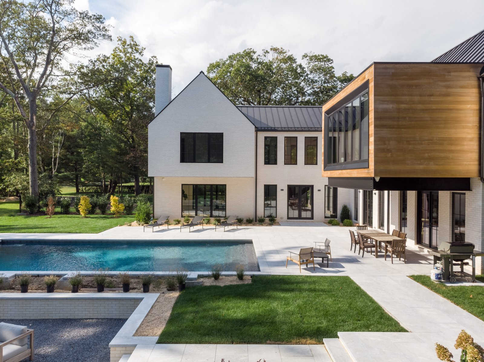 Outdoor, Concrete Pools, Tubs, Shower, Grass, Hardscapes, Back Yard, Landscape Lighting, Shrubs, Trees, Large Patio, Porch, Deck, and Large Pools, Tubs, Shower  Photo 1 of 11 in This Home's Unique Shape Is Designed to Capture Sunlight