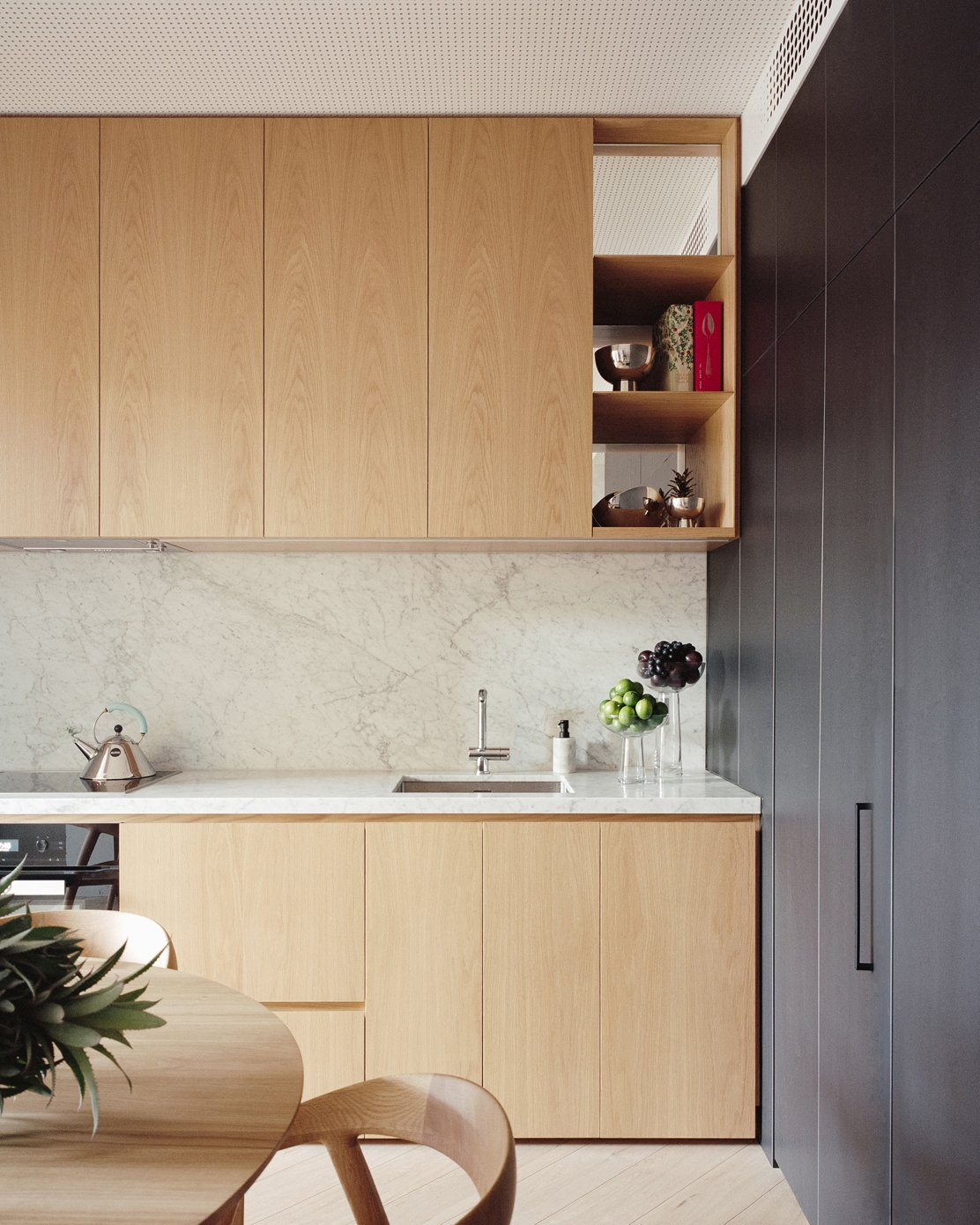 Kitchen, Wall Oven, Marble Counter, Undermount Sink, Medium Hardwood Floor, Marble Backsplashe, Wood Cabinet, and Cooktops  Photos from A Revamped Terrace House in Sydney Is an Audiophile's Dream
