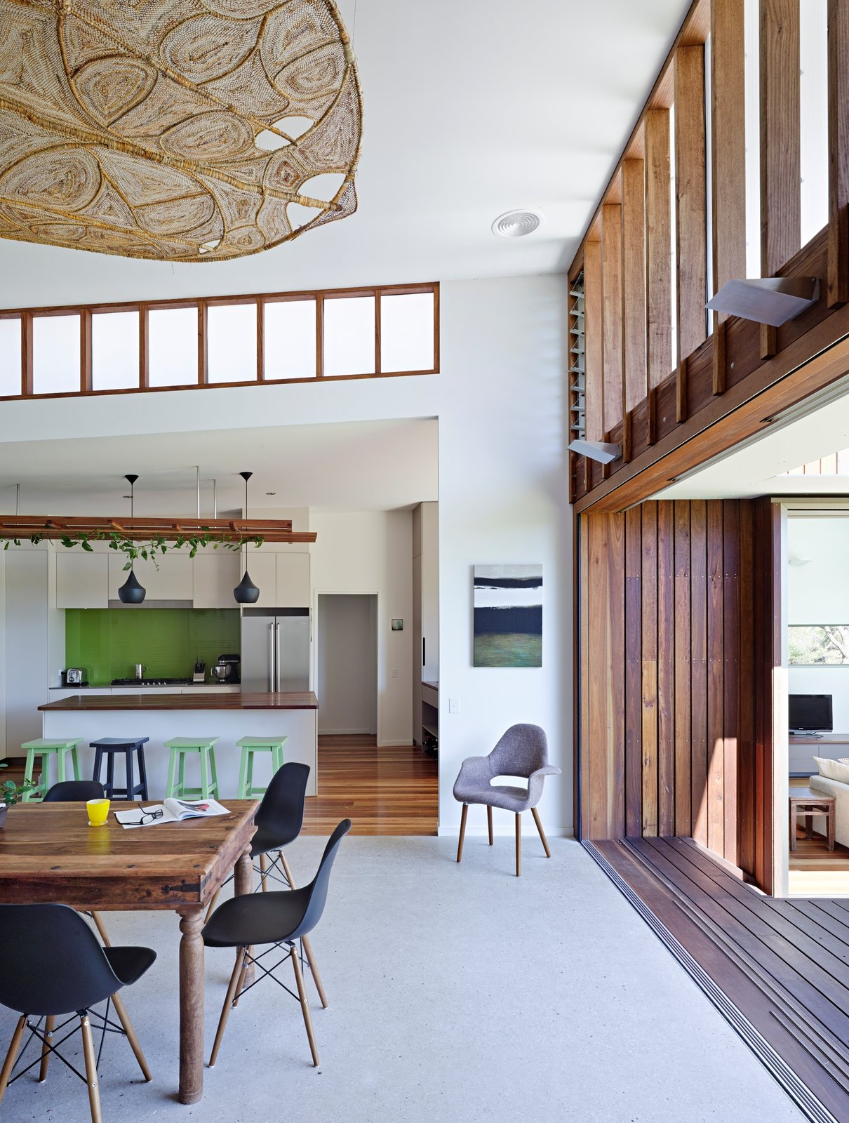 Dining Room, Ceiling Lighting, Table, Chair, Dark Hardwood Floor, Bar, Stools, and Rug Floor  Photo 4 of 10 in Vegetation Cocoons This Tranquil Beach House in Australia