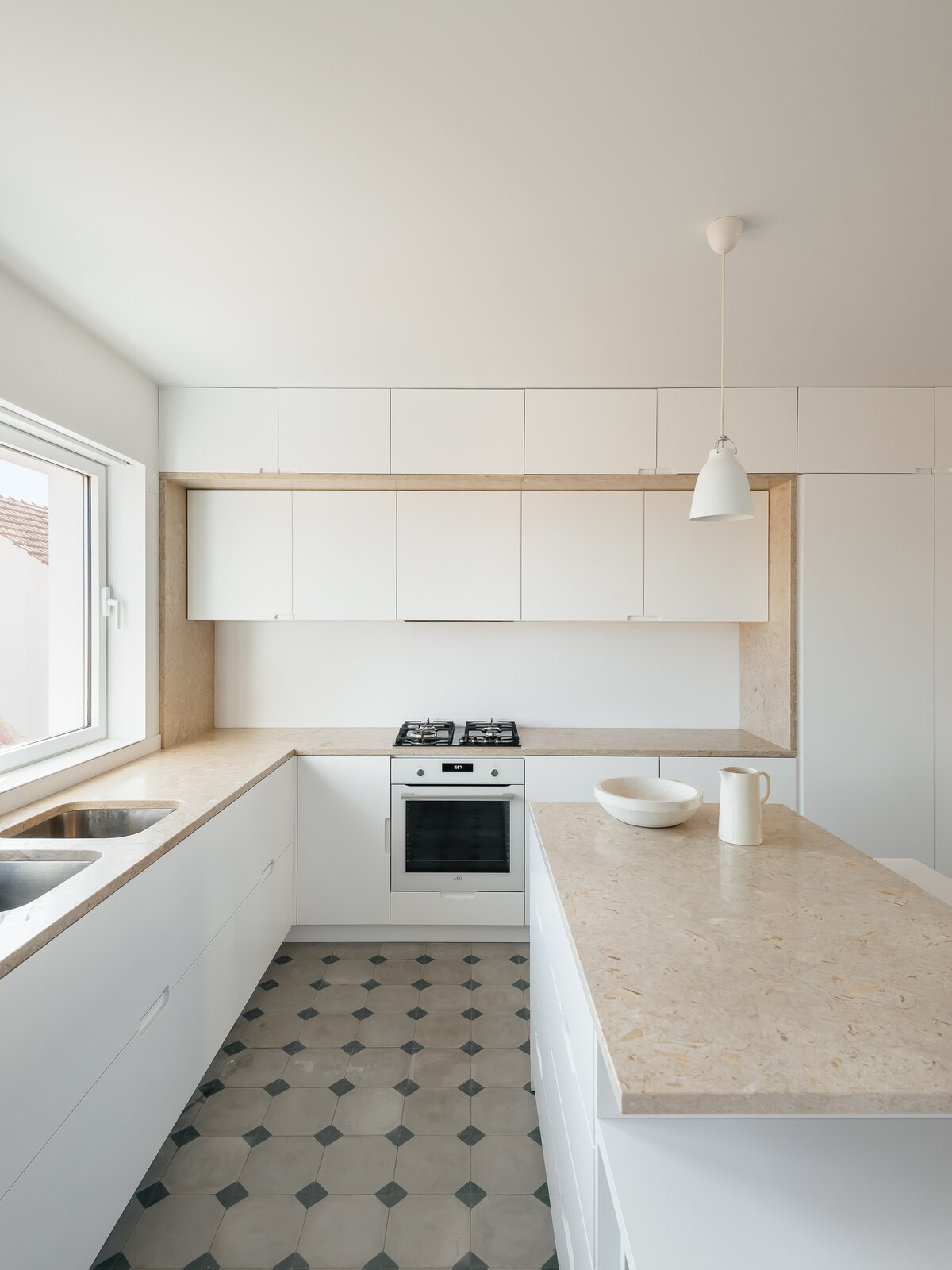 Kitchen, Stone Counter, Range, White Cabinet, Pendant Lighting, Wall Oven, and Drop In Sink  Photo 5 of 26 in A Hidden Fireman's Pole Is Just One of This Portuguese Home's Many Delights