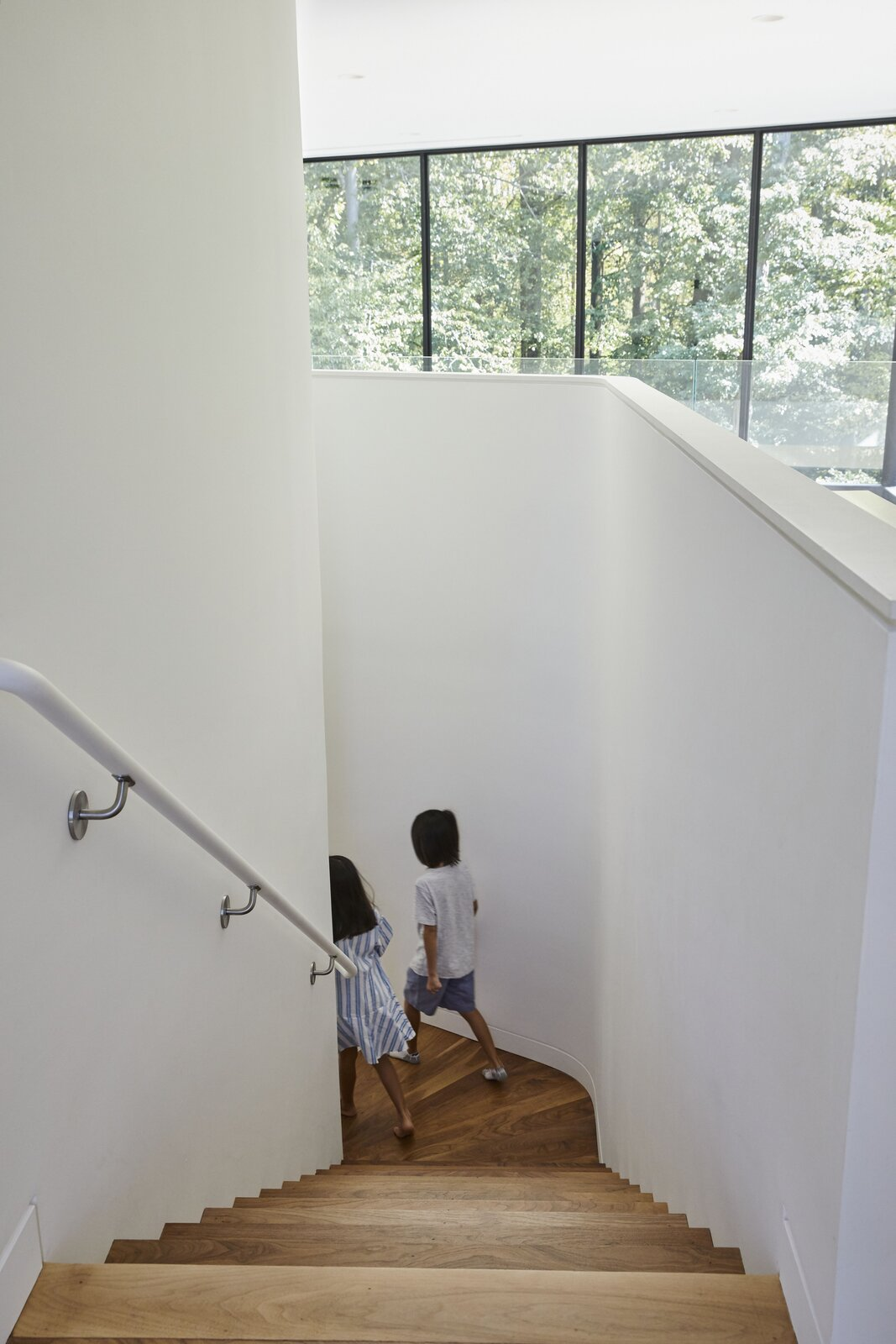 Staircase and Wood Railing  Photo 7 of 14 in At a Young Family's Woodsy Haven, a Soaring Living Space Anchors the Home
