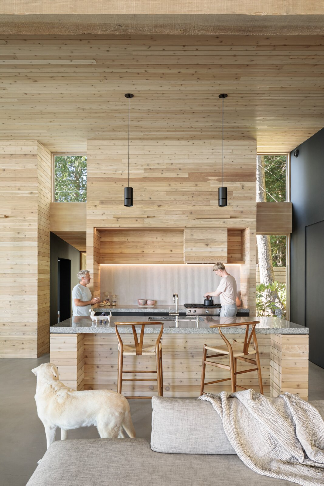 Kitchen, Track Lighting, Metal Cabinet, Granite Counter, Range Hood, Concrete Floor, Range, and Pendant Lighting  Dwell's Favorite Photos from An Angular Black Cabin Rises From the Woods Near Vancouver