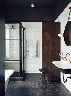 This Montreal bathroom is all about the mix of materials, from industrial metals and reclaimed wood to clean, graphic tiles.