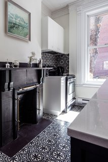 """""""We tried to keep the integrity of the [original] interior,"""" Havart says. """"We placed some cabinets around the beautiful but nonfunctional chimney."""" The oven is by Frigidaire."""
