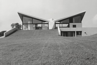 After declaring that he was done designing houses in the late 1960s, Breuer took a commission to design the Sayer House in France in 1972. He accepted only because the residents were willing to build a design that Breuer had proposed to another client in 1959. Its defining feature is a hyperbolic paraboloid roof made of board-formed concrete.