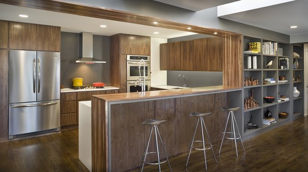 In a 1960s house in Overland Park, Kansas, Forward Design   Architecture remodeled a kitchen, family room, and mudroom. Walnut cabinets integrate the appliances to create a seamless look.