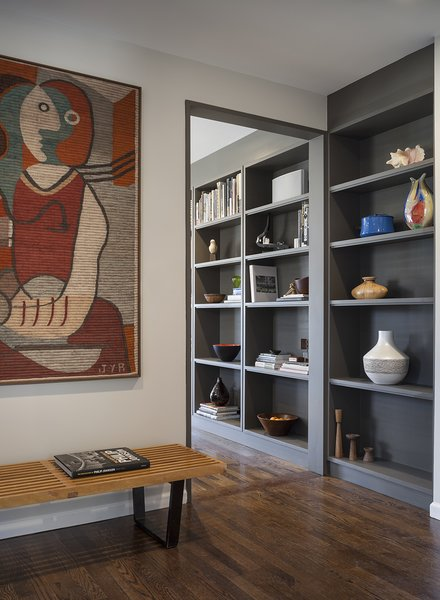 Transitioning from the eating bar, a wall of bookshelves carries through the space.