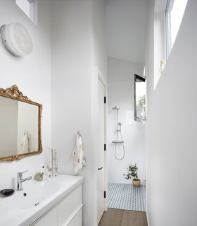 The en-suite master bathroom features an IKEA vanity and a curbless shower clad in Palau Celeste tile.