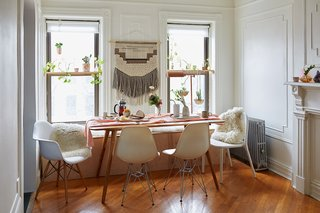500 Square Feet Is Just Right in Greenpoint - Photo 1 of 6 - The couple's changes to the space were mostly decorative. They built the custom bench in the dining area, which holds a litter box for their cat on one end and storage space on the other. The table was made by From The Source and the wall hanging is from CB2.