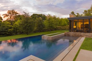 To enhance the home's floating effect, the rear yard features a pool that conceptually emerges from additional small pools of water that extend from under the house. Once the water reaches the backyard, it then flows over the infinity edge and back onto the landscape. Courtesy of Marvin Windows and Doors.