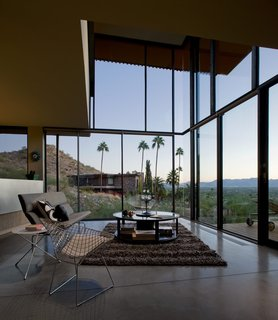 With floors made of cork and concrete, the house is surrounded by substantial panels of translucent glass. The double-height living room acts as a collective open space that looks out to the dramatic views of the desert.