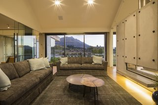 Constructed of precast concrete panels, this contemporary home in Queenstown, New Zealand was named the winner of the Gold and Lifestyle Awards at the 2015 Registered Master Builder House of the Year awards. Dividing the living and dining spaces, the slab fireplace runs the length of the living room and contrasts smoothly with soft timber woods that are utilized throughout the rest of the home.