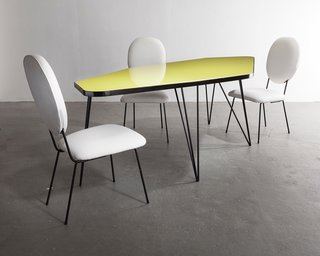 Also shown with Joaquim Tenreiro's edgy dining table, was a set of 1960s dining chairs with white leather upholstery and painted iron frames.
