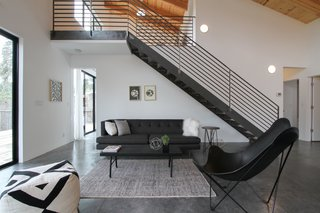 The living space sits underneath metal stairs that lead up to the mezzanine. Loewinger worked with a local metalworker to create the staircase. She purchased the furnishings from both HD Buttercup and CB2.