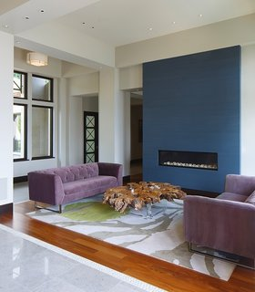 A closer look at the living space near the entrance reveals a modern fireplace that's built into a blue accent wall.