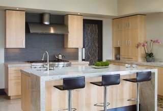 The kitchen features a waterfall counter made of the same marble that covers the rest of the surfaces.