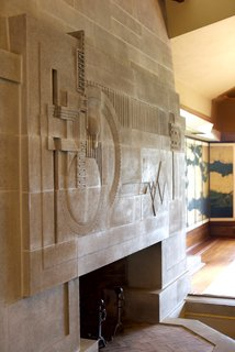 One of the standout moments in the space is the cast-concrete fireplace, which is considered to be one of Wright's greatest two-dimensional works of art. He completed the fireplace, a skylight above, and a moat that was designed to hold a pool of water. This was originally part of an elaborate water scheme to run through the property, though it was never completed.