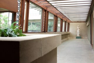 Since Wright was simultaneously working on the Japanese Imperial Hotel, he incorporated many Japanese details in the design of the Hollyhock House. Along with the Japanese screens in the living room, there's also a Buddhist sculpture at the end of a long hallway that's lined with art glass.