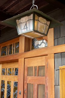 The home is surrounded by open porches that are constructed of cedar. The house's art glass—shown here on the front door—acted as a way to bring light into the space before there was electricity.
