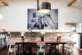 The base of the communal table is from Restoration Hardware while the custom copper table top is by Chris Mast. The restaurant is centered underneath a metal drum pendant light from Restoration Hardware and is finished with an authentic Greek photo-mural titled, The Guy in the Room by Nikos Economopoulos.
