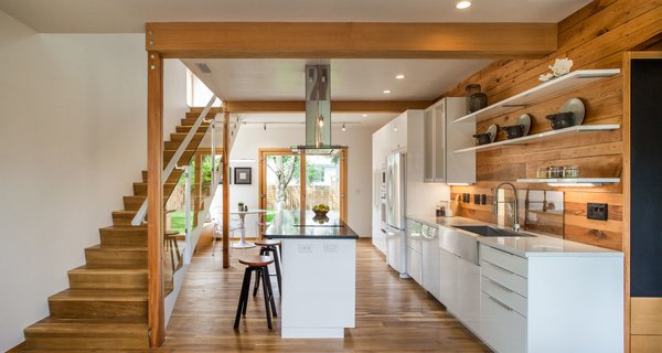 The interior is filled with a range of salvaged woods. Throughout the space, you'll find floors made of white oak from Oregon, reclaimed red oak, and cork. The open kitchen features quartz counters, an induction cooktop, and salvaged wood accents.