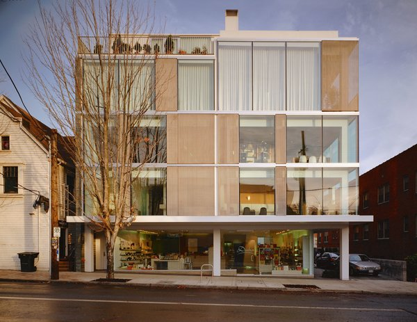 From the street view of the Glisan Street Residence, you can see the mix of materials that make up the structure including a steel frame, large expanses of windows, stainless steel mesh panels, and slate cladding. The ground floor hosts a storefront with floor-to-ceiling windows from one exposure.