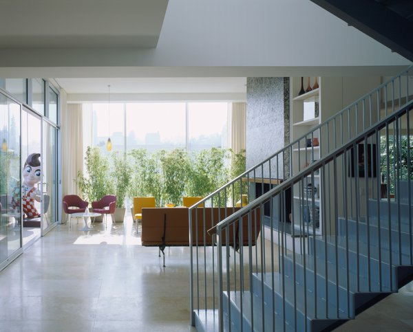 The interior features French limestone floors, glass mosaic wall tiles by Ann Sacks, and sliding glass doors from Kawneer.