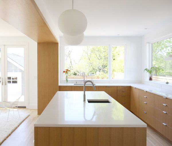 Robinson punched two large openings through the primary wall in the center of the house to create a larger, more inviting living environment. The kitchen includes white oak flooring, rift-cut white oak veneer cabinets, and ceramic tile from Heath.