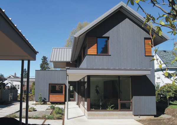 Interspersed throughout the gray siding are segments of horizontal natural finished cedar siding that they installed themselves. To fit with their active indoor/outdoor lifestyle, they included an exterior bike room that's accessible under the house's cover.