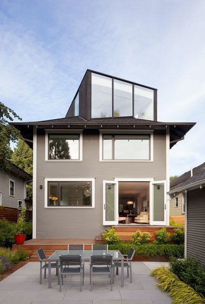 """Thomas Robinson of LEVER Architecture restored the exterior of the house in order to resurface the original wood facade, which had been covered up by vinyl siding at one point. They turned the unused attic into a """"FifthSquare"""": a box-like structure that acts as an office and mini-theater, complete with a ceiling-mounted projector and drop-down screen. The exterior of the extension is clad with charred cedar, which integrates smoothly into the asphalt shingle roof."""
