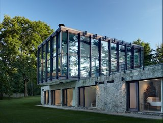 Shown here is a view of the stone and concrete structure that supports the cantilevered glass pavilion. The bottom section holds four bedrooms, bathrooms, and a sitting room. The glass and wood pavilion on top houses a combined living, dining, and kitchen space—all which is surrounded by 15-foot-tall windows.
