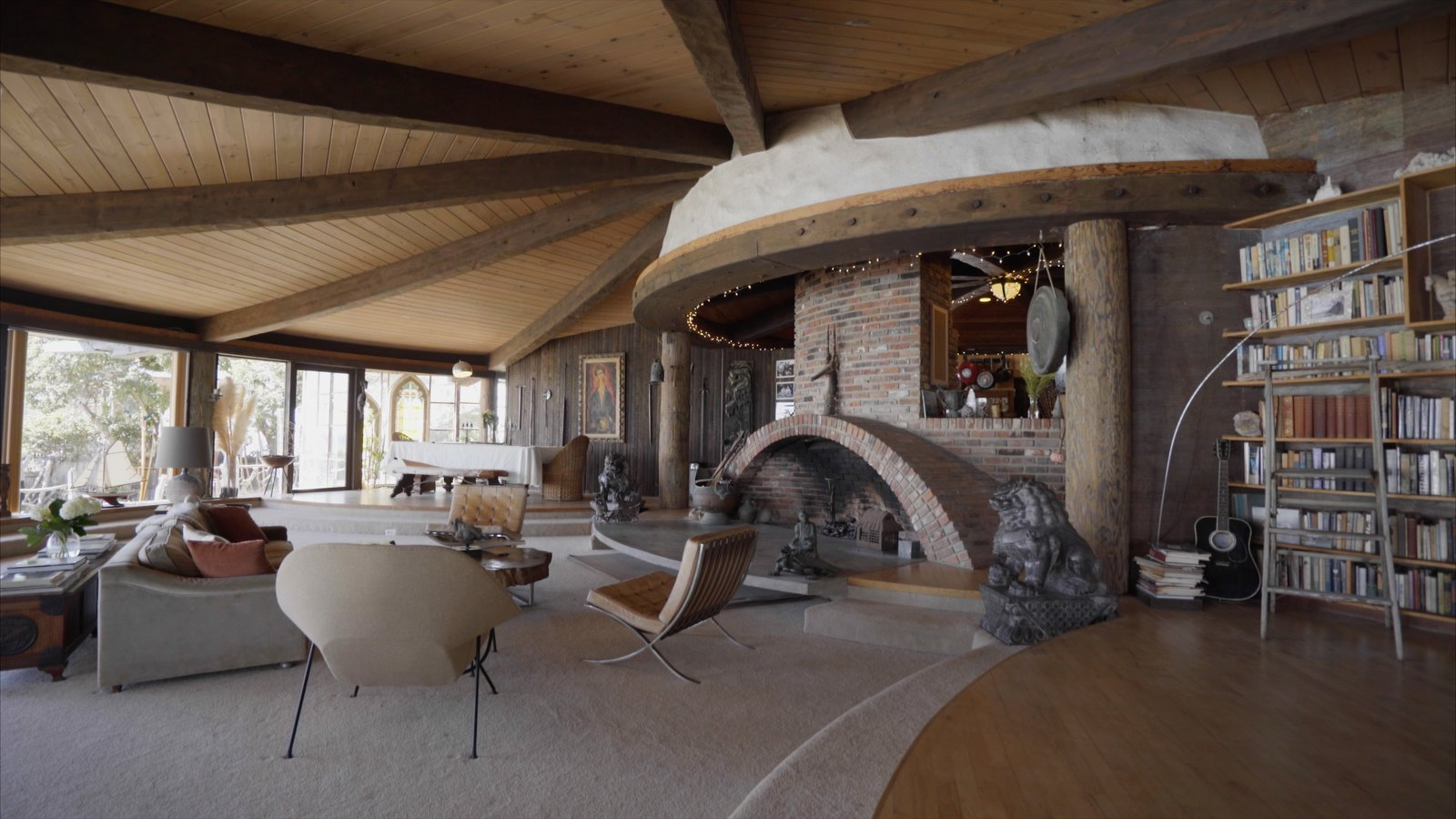 Living Room, Medium Hardwood Floor, and Wood Burning Fireplace #harrygesner #sandcastle #iconichouses  Video still courtesy of Jamie Leilani Pelayo  Photo 2 of 10 in 10 Modern Iconic Masterpieces