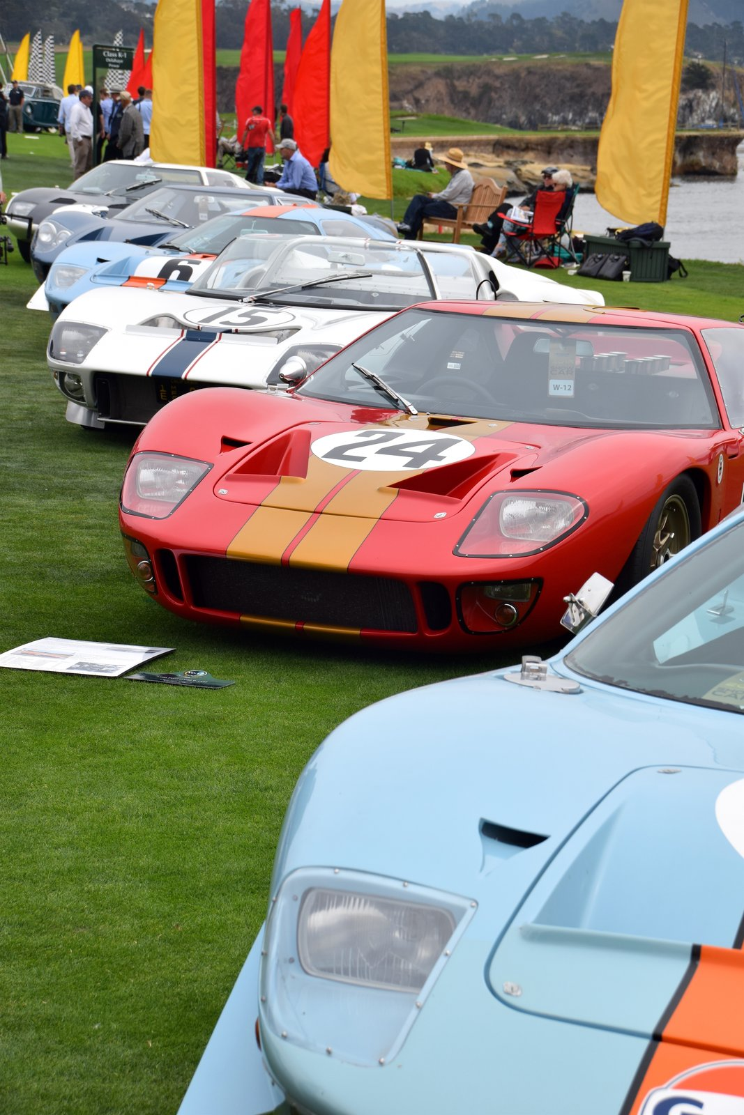 Lining the water on the 18th fairway of Pebble Beach Golf Links was a grouping of sporty race cars ranging from the '50s through the '70s—all of which had their own distinctive character and action-filled histories. The blue and orange car in the front is a 1968 Ford GT40 Mirage, which came from Sandy, Utah. During its time, it marked the first win for a sports car in the blue and orange Gulf livery, which has now become legendary. It also was used as a camera car in the film Le Mans by Steve McQueen.  Photo 2 of 10 in A Day at the Pebble Beach Concours d'Elegance Car Show