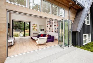 The second A-frame includes one end that's made up entirely of glass. It houses a spacious room that incorporates a kitchen, living room, and dining room.