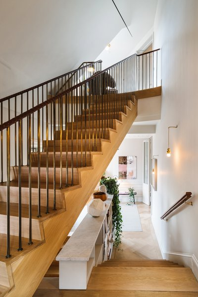 Though there's a small elevator that leads to each floor, there's also a wood-clad staircase with brass handrails that are wrapped with leather. You'll also find the owners' personal collection of art and photography that's spread throughout each floor.