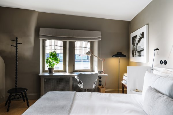 In this bedroom on the top floor, a desk area overlooks the Östermalm neighborhood and is equipped with heated floors. Each room also has its own brass cocktail cabinet.