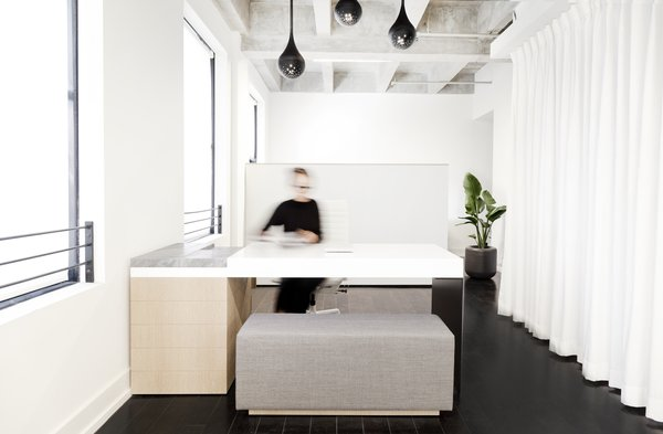 The custom appointment desk was designed and built with a single bent sheet of aluminum, lacquered MDF, marble, and white oak. The floor-to-ceiling white curtain hides the built-in kitchen that was part of Lee's loft from the beginning.