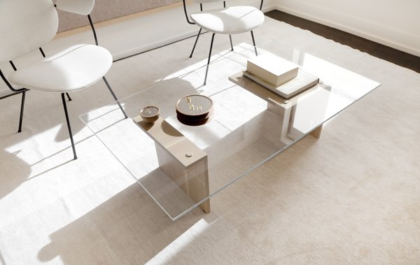 Jung and Hurewitz designed the custom angular glass and oiled oak coffee table, and set it next to a pair of vintage chairs. The round hand-turned walnut mirrors on the table were also custom produced and provide a space to showcase Lee's jewelry.