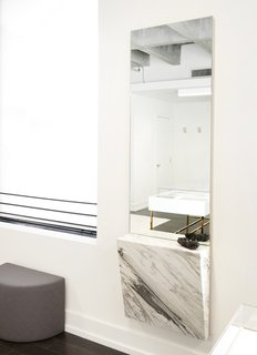 They affixed a chunk of Mountain Calcutta marble to a wall-mounted mirror to hold jewelry during fittings.