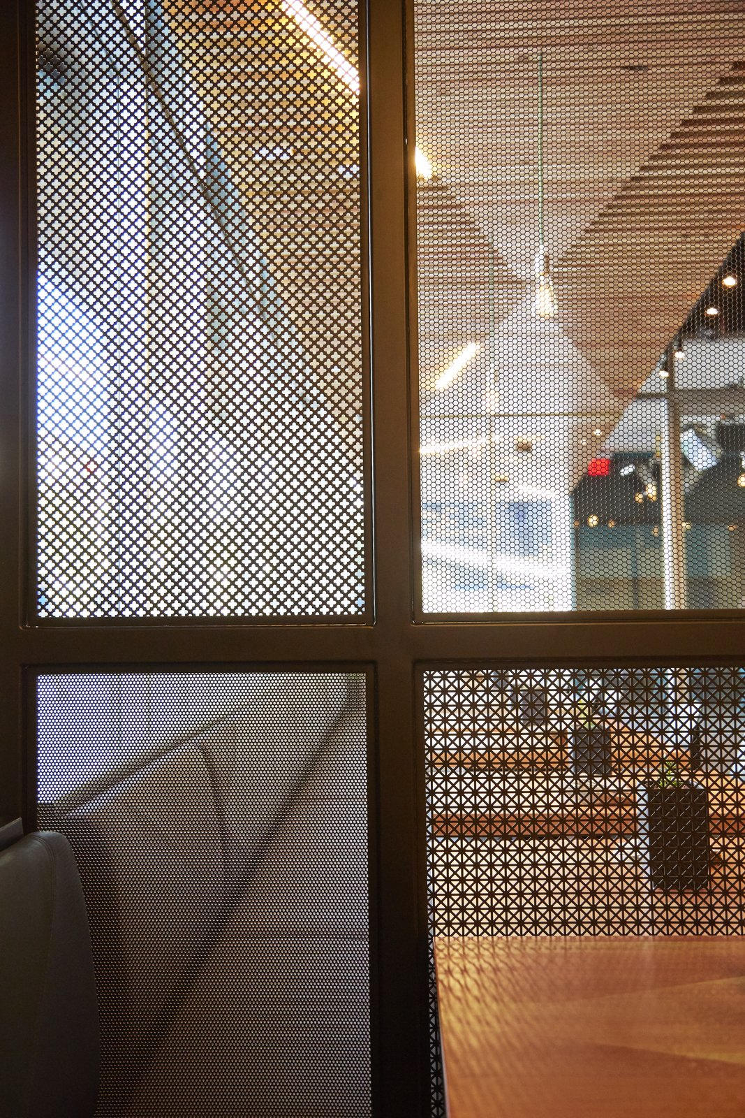 In order to help create privacy in certain areas at the Santa Monica locale, they created perforated metal screens that were inspired by traditional shoji screens.  Photo 8 of 9 in A Popular Burger Joint Flaunts Its Roots With the Help of a Design Collective