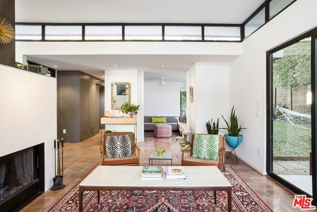 The open layout is connected to private gardens with floor-to-ceiling glass.  Photo 4 of 5 in A Glimpse Into a Remodeled Midcentury Abode in Austin