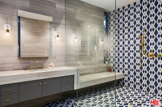 The master suite was completely updated with Carrera marble, travertine, and handmade encaustic tile that references elements of Stenger's original design.