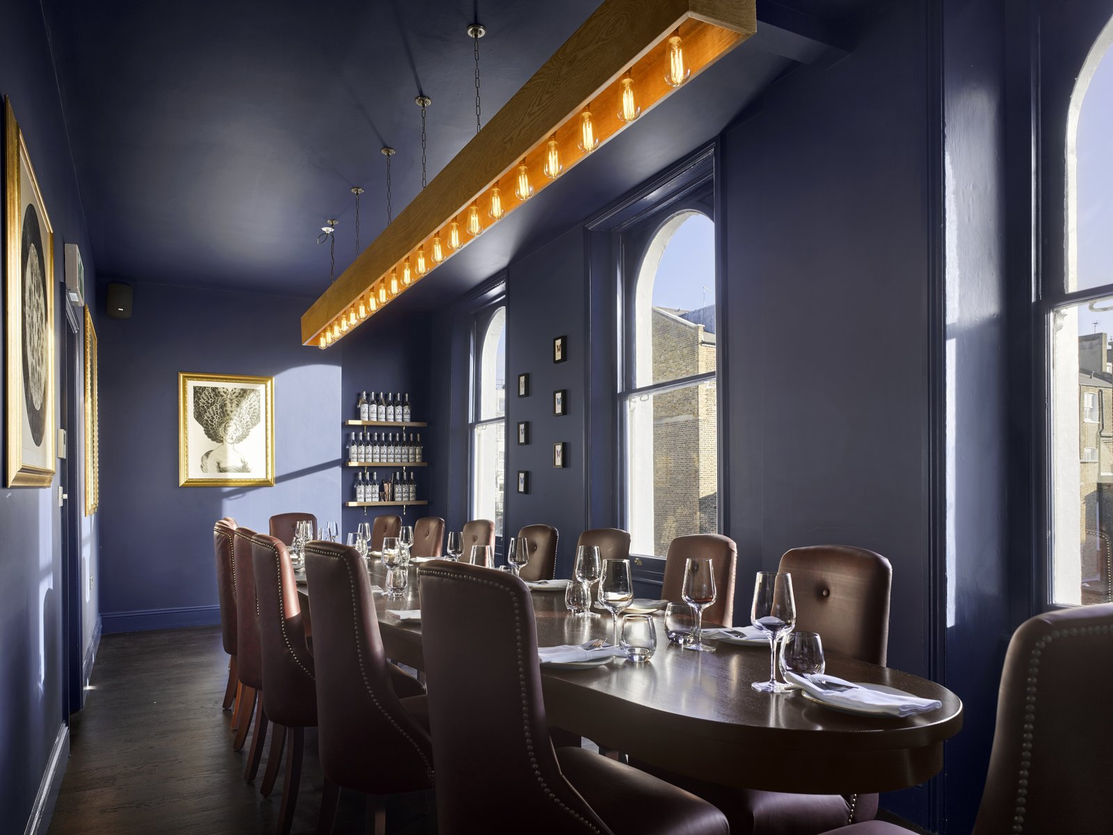 Dining Room, Chair, Table, Shelves, Pendant Lighting, and Dark Hardwood Floor On the top floor, you'll find The Boardroom, a private dining room that holds its own private bar.  Photo 6 of 7 in Gin Enthusiasts Will Be Flocking to This New London Hotel