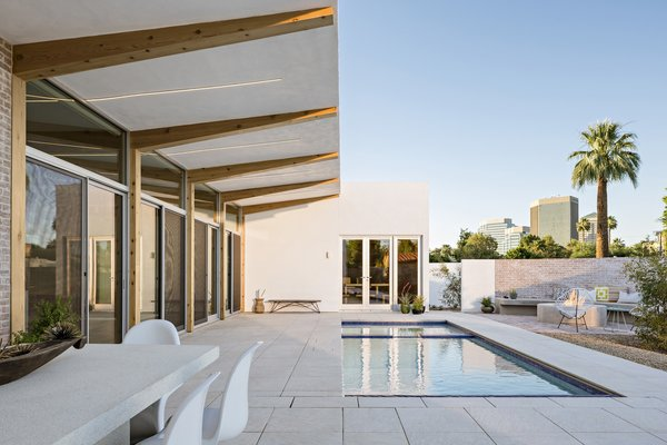 The U-shape courtyard-style house has a cantilevered roof that forms a sheltered outdoor living area—which allows breezes to flow directly into the living room when the doors are open.  Photo 2 of 3 in A Desert Oasis Awaits in a Historic District of Phoenix