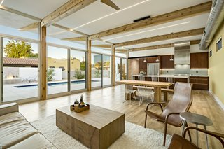 The wood beams and exposed brick from the exterior are reflected in the open living space, which also features a mix of natural surfaces and an exposed duct.