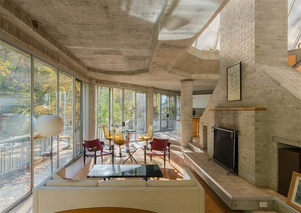 The living spaces and dining room are connected and feature an original fireplace. The concrete foundation is exposed throughout, accentuating the house's angular lines.  Photo 6 of 11 in The One-of-a-Kind Home of the Late Architect John Black Lee Drops to $750K